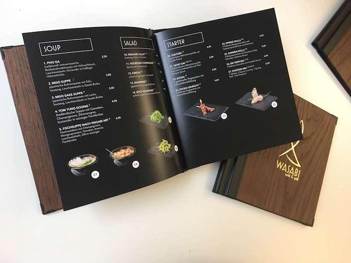 Die Speisen sind übersichtlich geordnet und die extra angefertigten Fotografien der Gerichte kommen auf dem schwarzen Hintergrund besonders zur Geltung